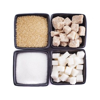 Tipos de açúcar em tigelas pretas isoladas no branco