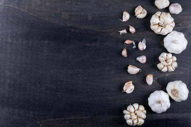 Tipos de alho no lado direito deitado em uma mesa de madeira escura