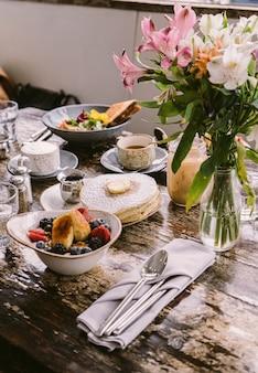 Tipos de alimentos, biscoitos e bebidas colocados na mesa em frente ao vaso de flores