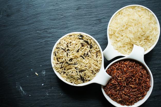Tipos de arroz em tigelas em uma mesa rústica