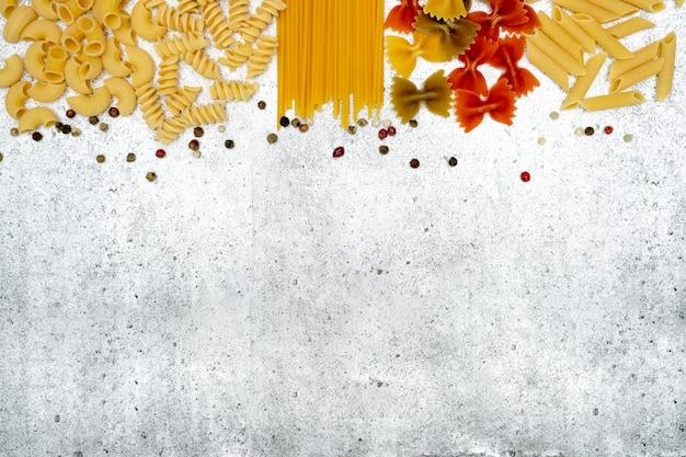 Tipos de macarrão cru. penne de macarrão, fusilli, farfalle, espaguete, chifferi e ervilhas coloridas secam sobre um fundo claro e concreto. . vista plana, vista superior, copyspace