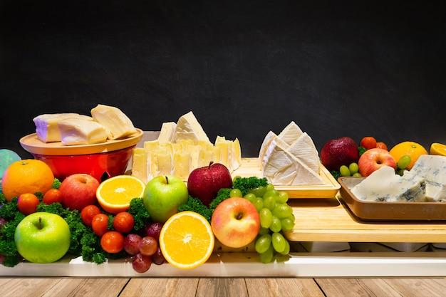 Tipos de queijo configuração em uma ampla gama de sabores na linha buffet com frutas decoração