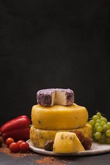 Tipos de queijo gourmet com variedade de vegetais, frutas e especiarias no preto