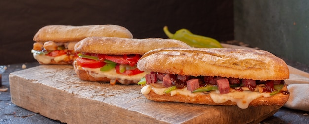 Tipos de sanduíche misto com vários alimentos em uma placa de madeira