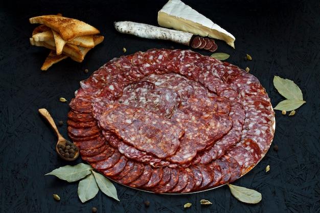 Tipos diferentes assorted de salsicha do queijo em um fundo escuro.