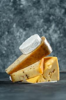 Tipos diferentes criativos de queijo que colocam no fundo escuro com espaço da cópia. camembert, queijo com especiarias, queijo holandês. grande cartaz para loja de queijos. fundo de alimentos. foco suave