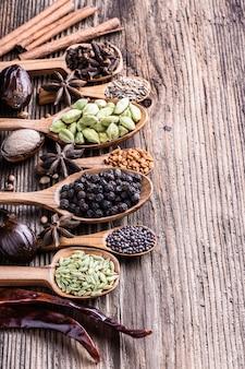 Tipos diferentes de especiarias indianas inteiras em close-up de madeira do fundo.