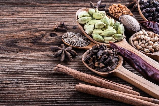 Tipos diferentes de especiarias indianas inteiras no close-up de madeira do fundo.