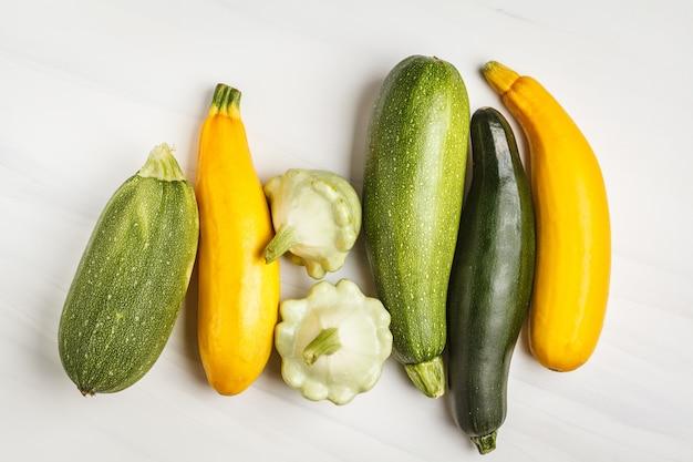 Tipos diferentes do abobrinha no fundo branco, vista superior, espaço da cópia. conceito de comer limpo e saudável.