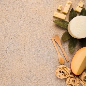 Tipos frescos saborosos de queijos com macarrão cru; folhas de louro e colher de pau sobre a superfície de textura de mármore