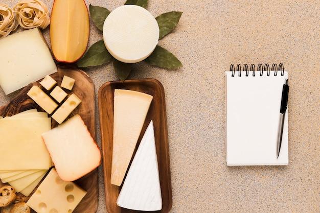 Tipos saudáveis de queijos na placa de madeira com o bloco de notas e a pena brancos em branco