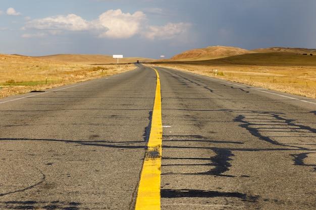 Tira contínua amarela na estrada de asfalto