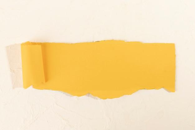 Tira de papel amarela torta em um fundo rosa pálido