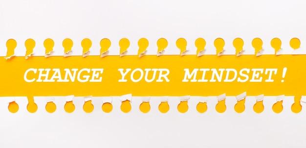 Tira de papel rasgada em fundo amarelo com o texto mude sua mentalidade