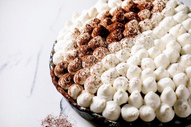 Tiramisu caseiro sem glúten tradicional sobremesa italiana polvilhado com cacau em pó sobre mesa de mármore branco