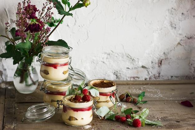 Tiramisu de sobremesa caseira com framboesas na jarra de vidro
