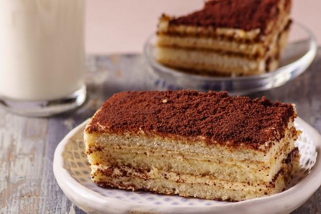 Tiramisu do bolo - sobremesa deliciosa em uma placa, com um vidro do leite no fundo.