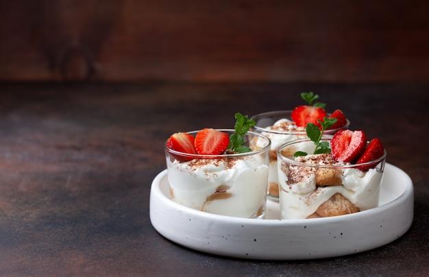 Tiramisu em um copo com morangos frescos