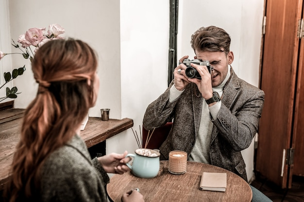 Tirando foto de filme. um homem está tirando uma foto de uma mulher usando uma câmera de filme