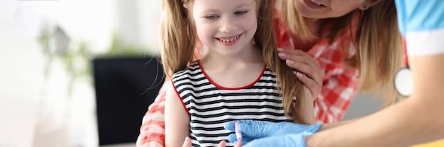 Tirando sangue do dedo de meninas para análises laboratoriais