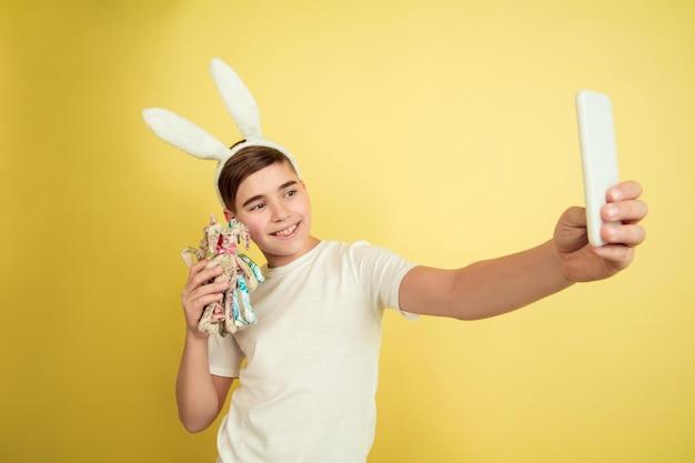 Tirando selfie com brinquedo. menino caucasiano como um coelhinho da páscoa em fundo amarelo do estúdio. saudações de páscoa feliz.
