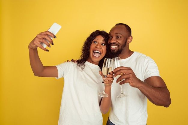 Tirando selfie juntos. casal afro-americano feliz isolado na parede amarela. conceito de emoções humanas, expressão facial, amor, relações, férias românticas.