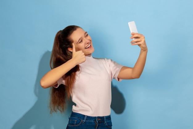 Tirando selfie ou vlog, sorrindo, polegar para cima. retrato de uma menina adolescente caucasiana sobre fundo azul. bela modelo em casual. conceito de emoções humanas, expressão facial, vendas, anúncio. copyspace. parece feliz.