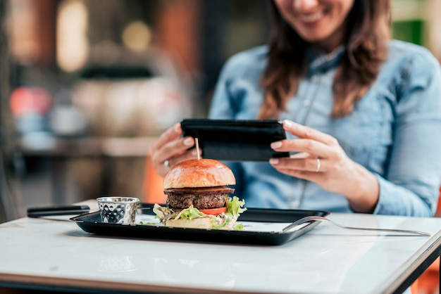 Tirando uma foto de hambúrguer saboroso. concentre-se no primeiro plano, no hambúrguer.
