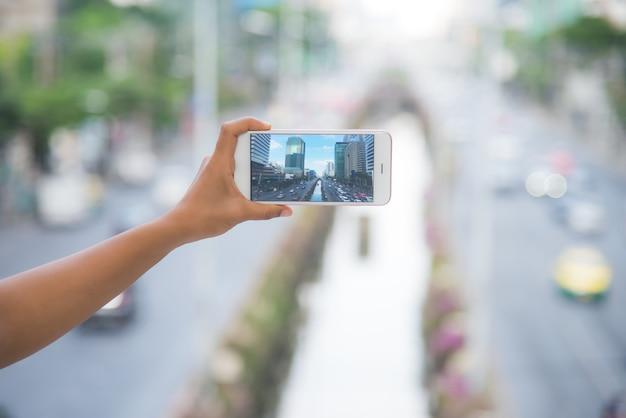 Tirando uma foto de uma torre da cidade em banguecoque, tirando foto com smartphone
