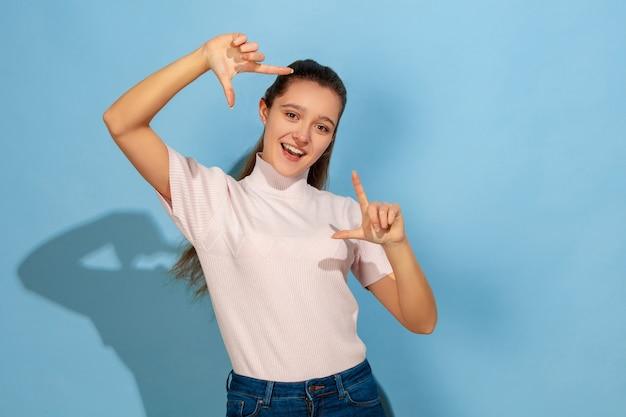 Tirando uma selfie, enquadrando. retrato de uma menina adolescente caucasiana sobre fundo azul. bela modelo em moda casual. conceito de emoções humanas, expressão facial, vendas, anúncio. copyspace. parece fofo, feliz.