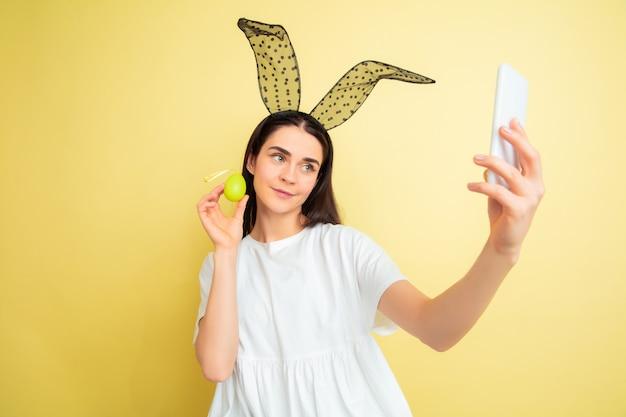 Tirando uma selfie. mulher caucasiana como um coelhinho da páscoa em fundo amarelo studio. saudações de páscoa feliz. lindo modelo feminino. conceito de emoções humanas, expressão facial, feriados. copyspace.