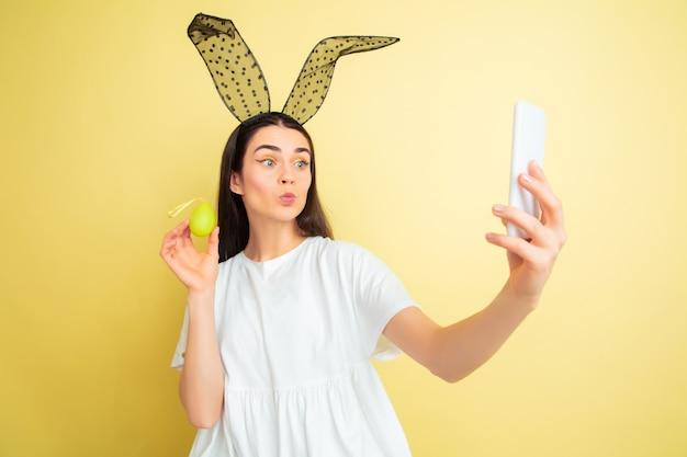 Tirando uma selfie. mulher caucasiana como um coelhinho da páscoa em fundo amarelo.