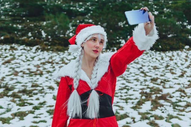 Tirando uma selfie vestida como a sra. claus no natal