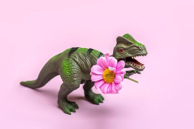 Tiranossauro de brinquedo segurando uma flor de margarida