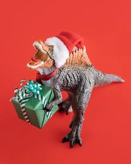 Tiranossauro rex segurando uma caixa de presente