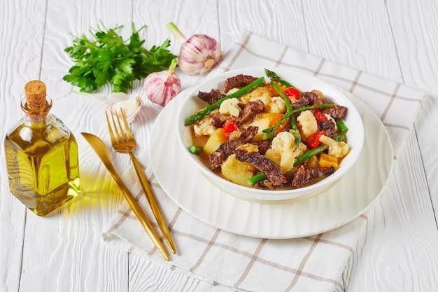 Tiras de carne no verão ensopado com batatas novas, aspargos e couve-flor em uma tigela branca sobre uma mesa de madeira, cozinha americana, vista da paisagem
