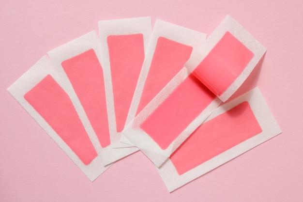 Tiras de cera rosa para depilação em um fundo rosa. depilação, depilação, remoção de pelos indesejados