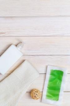 Tiras de cera verdes com efeito de menta e resfriamento, hidratante corporal e toalha de algodão branco na madeira