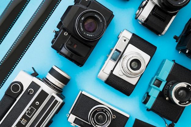 Tiras de filme perto de câmeras fotográficas e de vídeo