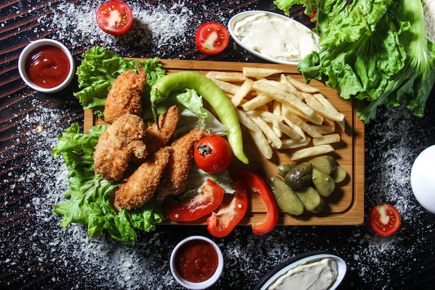 Tiras de frango frito com batatas, ervas e picles