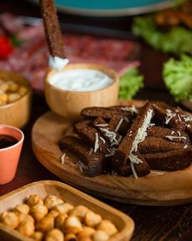 Tiras de pão preto com ralos de alho, óleo e queijo por cima e iogurte
