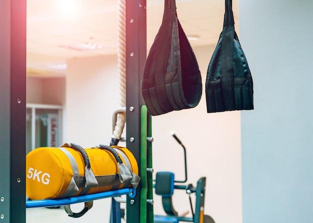 Tiras de treinamento trx penduradas na parede e saco amarelo com 5 kg no ginásio.