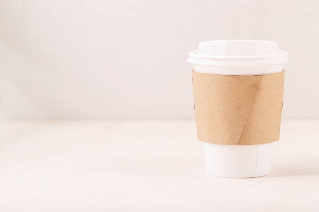 Tire a xícara de café de papel com espaço para o logotipo na xícara sobre fundo branco. copie o espaço