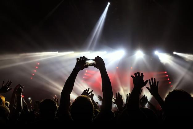 Tire foto com smartphone em frente ao palco do show, durante o show de luzes