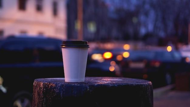 Tire o espaço vazio da cópia em branco da xícara de café para o seu texto de design ou banner da marca, bebida quente na mesa de madeira com uma bela decoração com luz da cidade