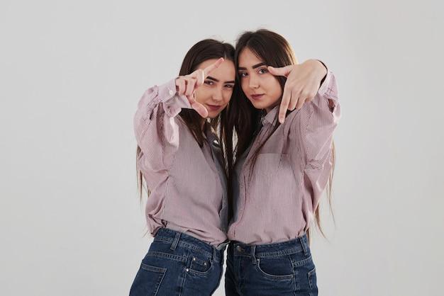 Tire uma foto nossa. duas irmãs gêmeas em pé e posando