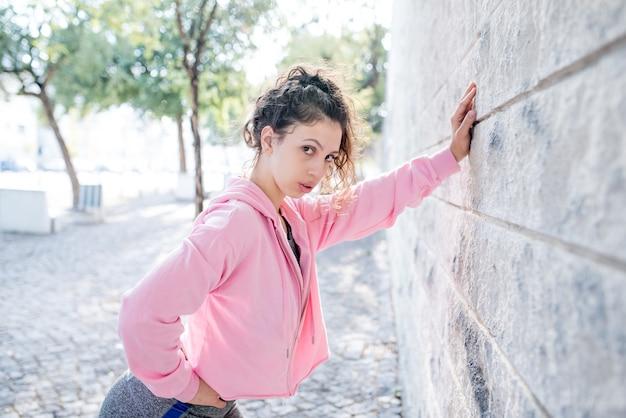Tired sporty pretty girl inclinada na parede