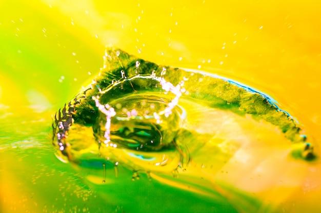 Tiro abstrato surpreendente do respingo da gota da água na folha verde na água.