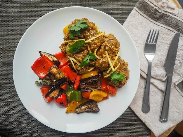 Tiro aéreo closeup de alimentos cozidos do oriente médio em um prato branco com um garfo e uma faca de cozinha