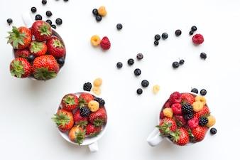 Tiro aéreo de bagas frescas saudáveis coloridas em copos em um fundo branco